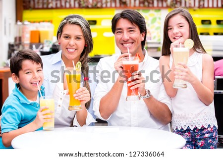 Happy family at a cafeteria drinking fresh juices - stock photo