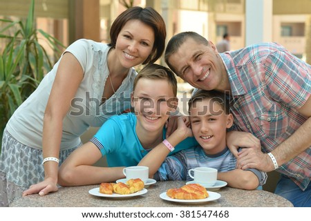 Happy family at breakfast on the table - stock photo