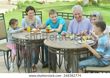 Happy family at breakfast on tropical resort - stock photo