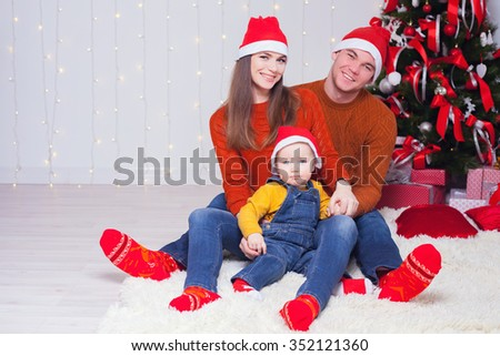 Happy family at Christmas eve sitting together near decorated tree at living room, home. Concept of celebrating New Year holiday at Russia. Father, mother and boy looking at camera. - stock photo