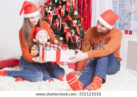 Happy family at Christmas eve sitting together near decorated tree at living room, home. Father giving gift to baby and mother looking at child. New Year. - stock photo