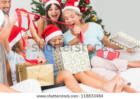 Happy family at christmas opening gifts together on the couch - stock photo