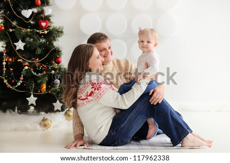 Happy family at Christmas. Parents look at the child. Kid looks at us. In the background stands and Christmas tree ornaments. - stock photo