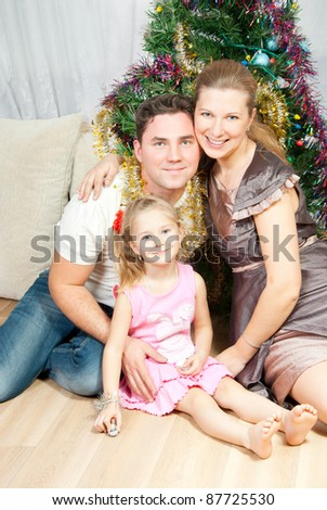 Happy family at Christmas spruce - stock photo