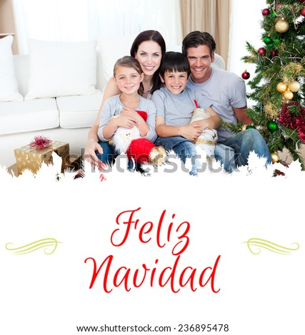Happy family at Christmas time holding lots of presents against border - stock photo