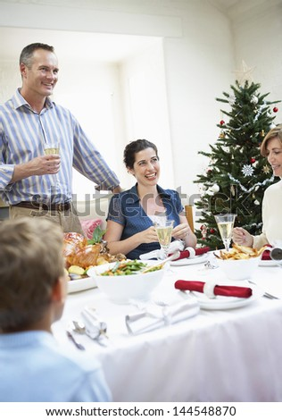 Happy family at dinner table enjoying food on Christmas - stock photo