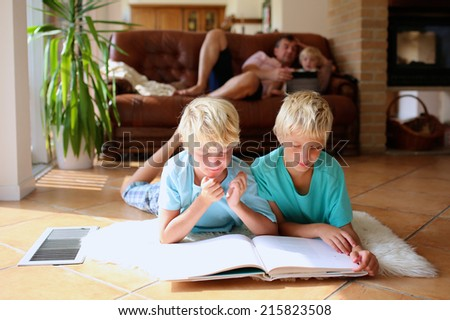 Happy family at home, bright sunny classic living room with tiles floor and big windows - two brothers reading lying on the floor, father with daughter playing on sofa at background - stock photo