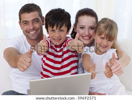 Happy family at home using a laptop with thumbs up - stock photo