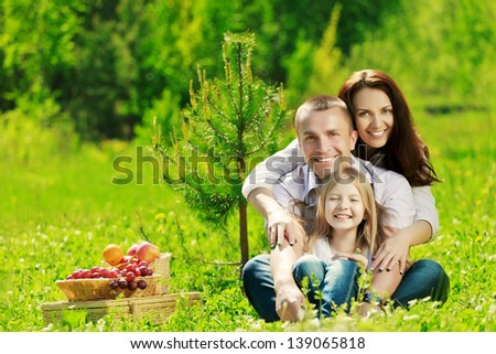 Happy family at picnic on the summer meadow - stock photo