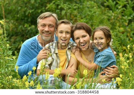 Happy family at summer green blooming field - stock photo