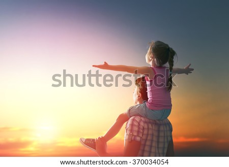 happy family at sunset. father and daughter having fun and playing in nature. the child sits on the shoulders of his father. - stock photo