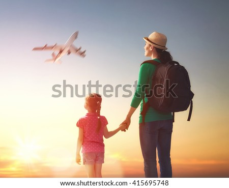 happy family at sunset. mother and her child daughter looking at the flying plane in the sky. - stock photo