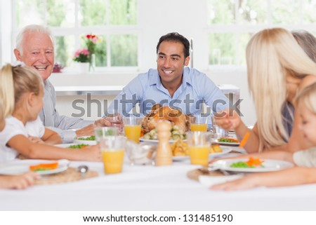 Happy family at the dinner table at thanksgiving - stock photo