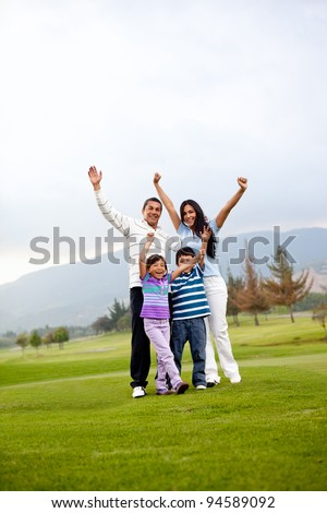 Happy family at the golf course with arms up - stock photo