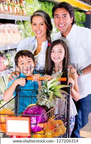 Happy family at the grocery store looking very happy - stock photo