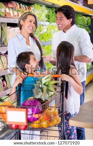 Happy family at the supermarket grocery shopping