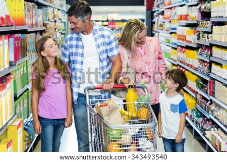 Happy family at the supermarket with cart