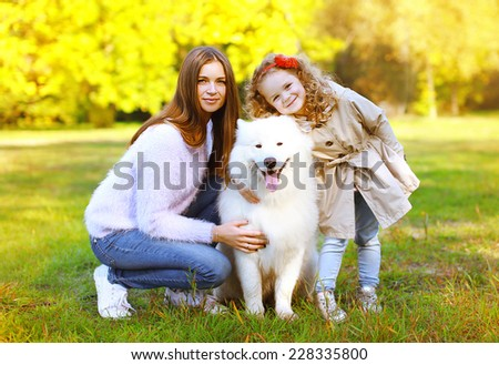 Happy family autumn, portrait pretty young mother and child walks with dog outdoors in the park - stock photo