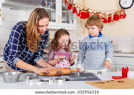 Happy family baking Christmas cookies at home. Little boy, girl and mother having fun in domestic decorated kitchen. Traditional leisure with kids on Xmas - stock photo