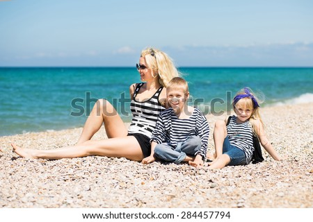 Happy family: beautiful woman and her adorable son and daughter relaxing on the beach - stock photo