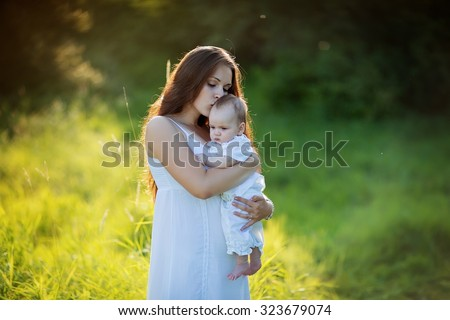 Happy family: beautiful young mother in white clothes walking with her new-born daughter in the park on a sunny summer day.  - stock photo