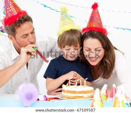 Happy family blowing candles together for a birthday at home