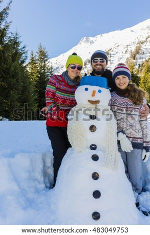Happy family building snowman and playing in fresh snow at beautiful sunny winter day in swiss Alps