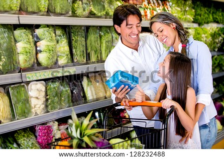 Happy family buying healthy food at the supermarket - stock photo