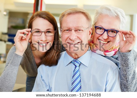Happy family buying new glasses at optician retail store - stock photo