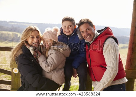 Happy family by a gate in the countryside, close up - stock photo