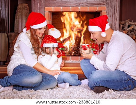 Happy family by fireplace, parents with baby girl wearing Santa Claus hats, sitting relaxed in ski resort chalet and drinking hot tea, joyful winter vacation, people traveling on Christmas holidays - stock photo