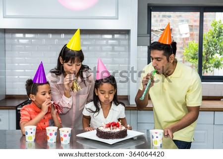 Happy family celebrating a birthday at home in the kitchen - stock photo