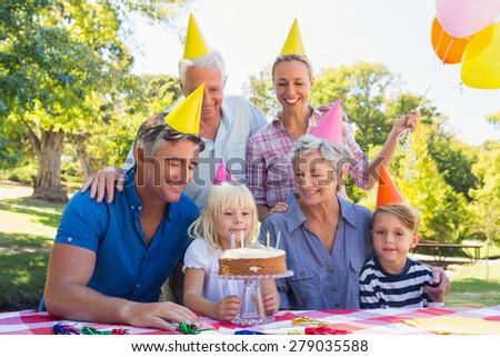 Happy family celebrating a birthday on a sunny day - stock photo