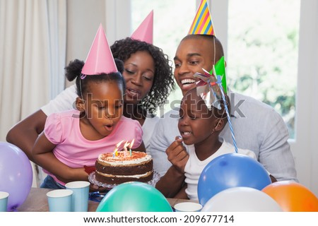 Happy family celebrating a birthday together at home in the kitchen - stock photo