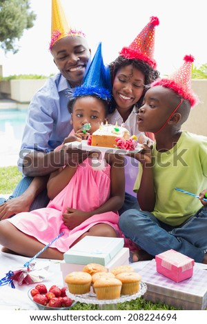 Happy family celebrating a birthday together in the garden on a sunny day - stock photo