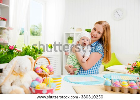 happy family celebrating easter mother and baby bunny ears at home with colorful eggs and flowers