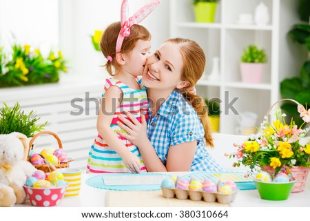 happy family celebrating Easter. mother and daughter kissing at home with decorations multi colored eggs and flowers - stock photo