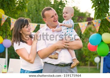 Happy family celebrating first birthday of baby son - stock photo