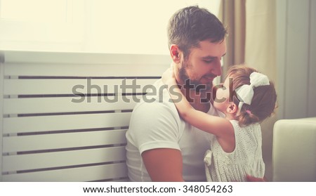 happy family child baby girl in the arms of his father at home window
