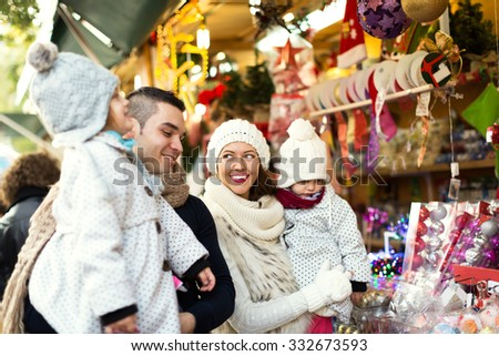 Happy family choosing Christmas decoration at Christmas market. Focus on woman and her daughter