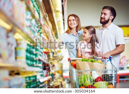 Happy family choosing dairy products in supermarket - stock photo