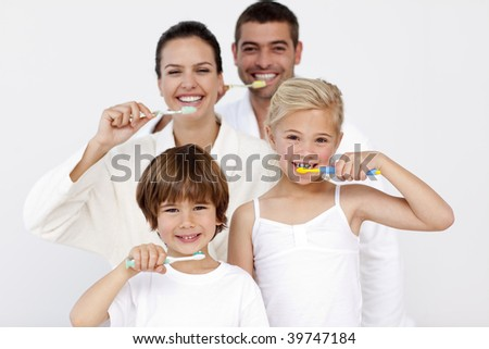 Happy family cleaning their teeth in bathroom