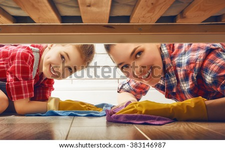 Happy family cleans the room. Mother and daughter do the cleaning in the house. A young woman and a little child girl wiped the floor.
