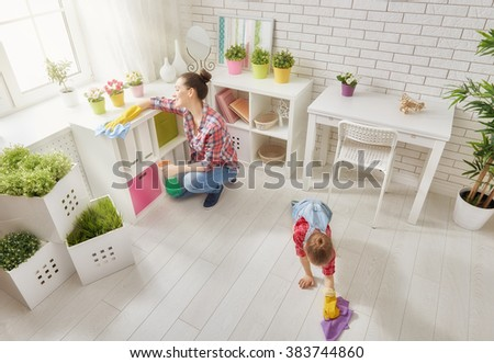 Happy family cleans the room. Mother and daughter do the cleaning in the house. A young woman and a little child girl dusting. - stock photo