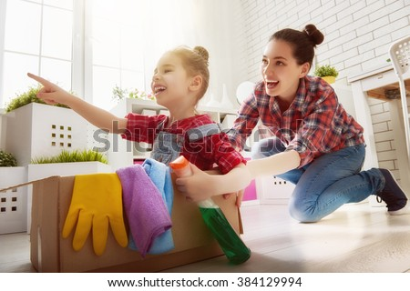 Happy family cleans the room. Mother and daughter do the cleaning in the house. A young woman and a little child girl having fun and riding in cardboard boxes at home. - stock photo
