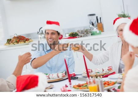 Happy family clinking their glasses of white wine for christmas - stock photo