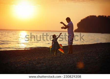 Happy family concept: a young man helps his little daughter to fly a kite on the sea coast against sunset sky and mountains on a warm summer day.
