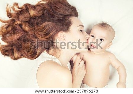 Happy family concept. Beautiful young red haired mother kissing her cute little baby. - stock photo