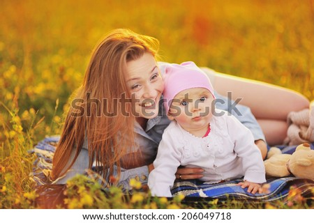 Happy family concept, mom and lovely daughter at sunny field.