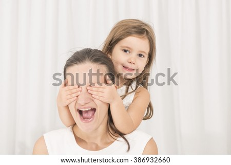 Happy family concept. Mother and her little lovely daughter, concept of togetherness, studio shot. Mother and daughter having fun playing - stock photo